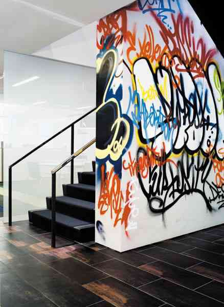 beautiful contrast between the angular lines and sober colors of the floor and wall and the vibrant colored, flowing lines of the graffiti